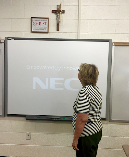 Ms. Fraser looks at the crucifix hanging above her Smartboard.