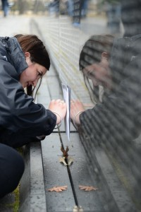 Kylie Best traces over the the name of a family friend on the Vietnam Memorial Wall