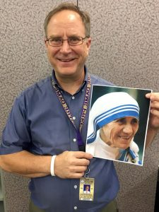 Theology teacher Dr. Stephen Matuszak, who met Mother Teresa, holds a picture of her.