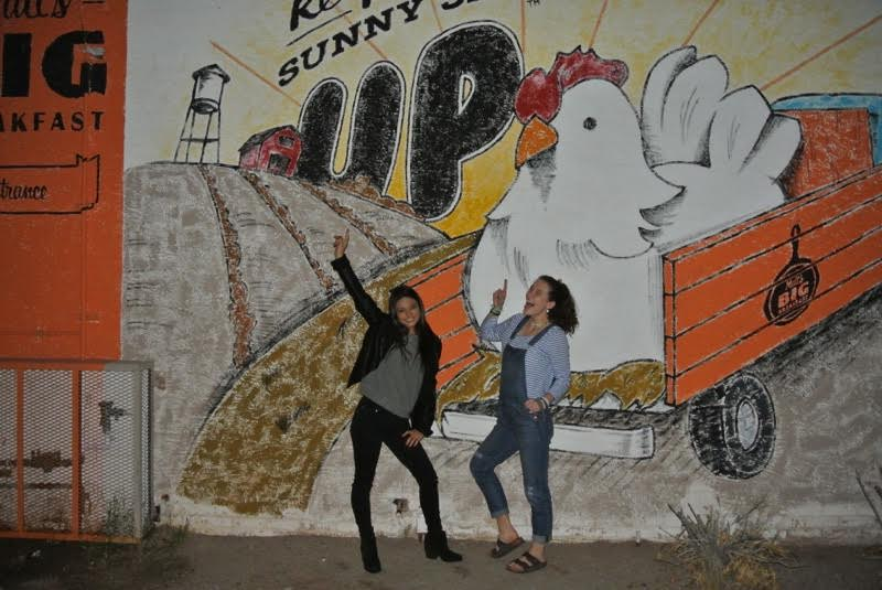 Seniors Mariana Galindo and Shannon Belknap pose in front of a mural.