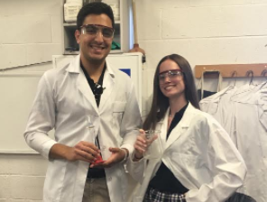 Seniors Brij Kathuria and Kiley Nelson don lab coats in AP Biology class.
