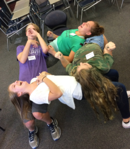 (From left, Will Goldwater, Tori Goebel, Sophie Cartwright, and Ashton Rains form a human table in Leadership workshop (Anna Sera/The Seraphim)