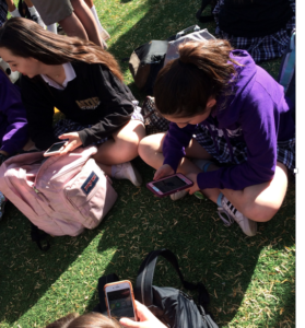 A group of NDP freshmen gather over cell phones during break (Anna Sera/The Seraphim)