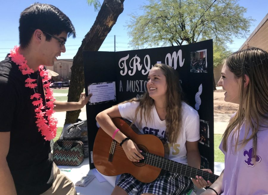 Senior Sebastian Beller talks to Guitar Club members at the fair.