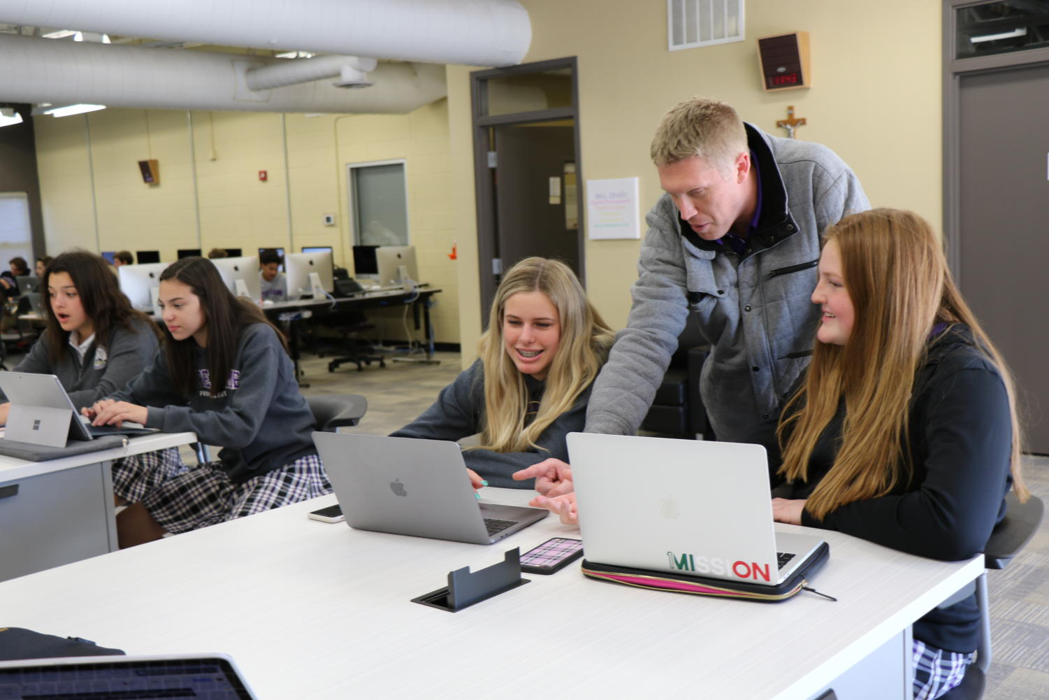 Above: Technology teacher Kyle Diemer helps students in his Innovation and Design Based Thinking class, a new addition to the freshman curriculum at NDP.  Photo from ndpsaints.org